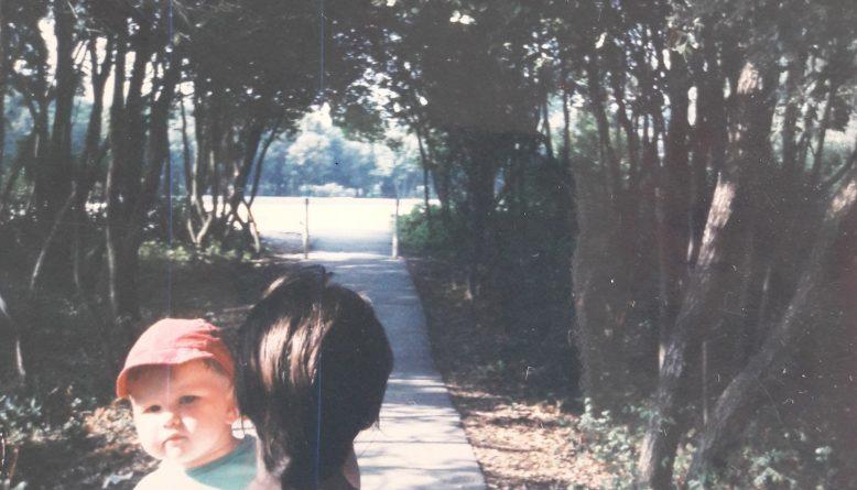 Majka koja je leđima okrenuta kameri u naručju nosi dijete koje preko njezinog ramena gleda u kameru.