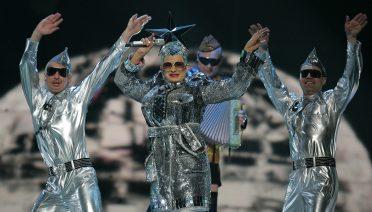 Verka Serduchka i njezini plesači plešu visoko podignutih ruku za vrijeme nastupa na Euroviziji.