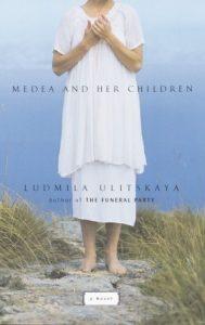 """Naslovnica engleskog prijevoda teksta Ljudmile Ulicke pod naslovom """"Medea and Her Children"""". Bosonoga osoba u bijeloj haljini stoji na pijesku, more je u pozadini."""