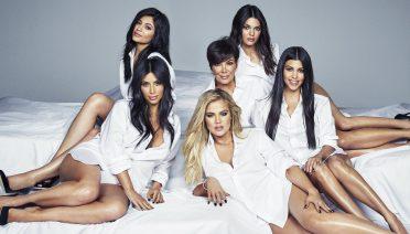 Sestre Kardashian i Jenner zajedno s majkom Chris sjede na krevetu. Odjevene su u identične bijele košulje i gledaju u kameru.
