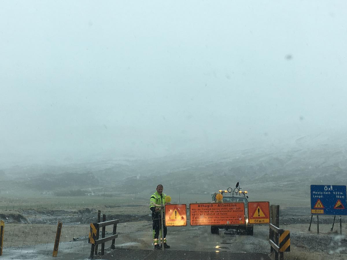 Zatvorena cesta. Čovjek i narančasti znak koji zabranjuje prolaz, magla i planina u pozadini