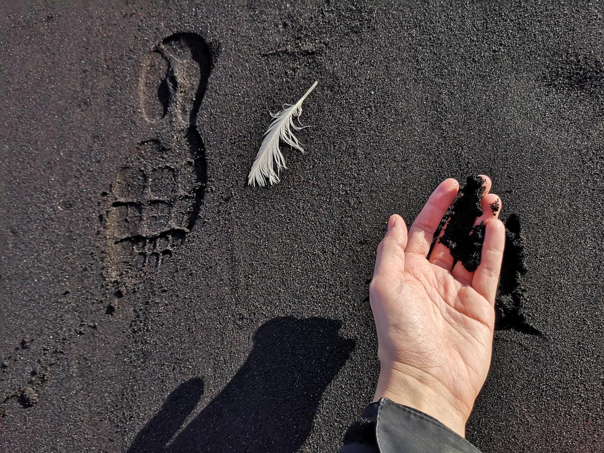 Crni pijesak na kojem je bijelo pero i ruka koja drži crni pijesak