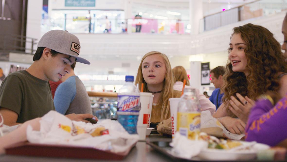 Dvije djevojke i dečko za stolom a pred njima junk food