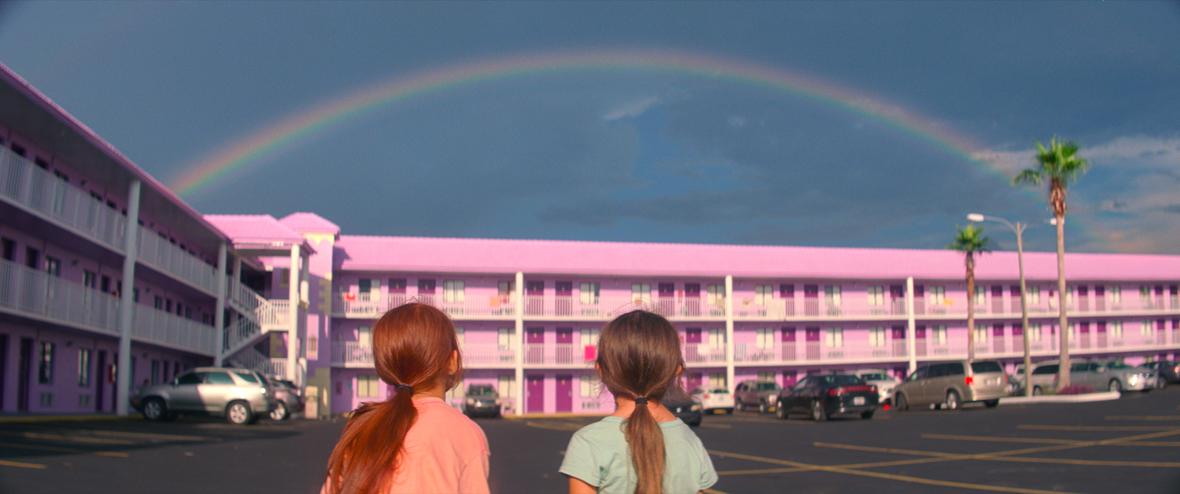 Dvije djevojčice s leđa, jedna crvenokosa a jedna smeđokosa, gledaju u zgradu ružičaste boje iznad koje je na nebu duga