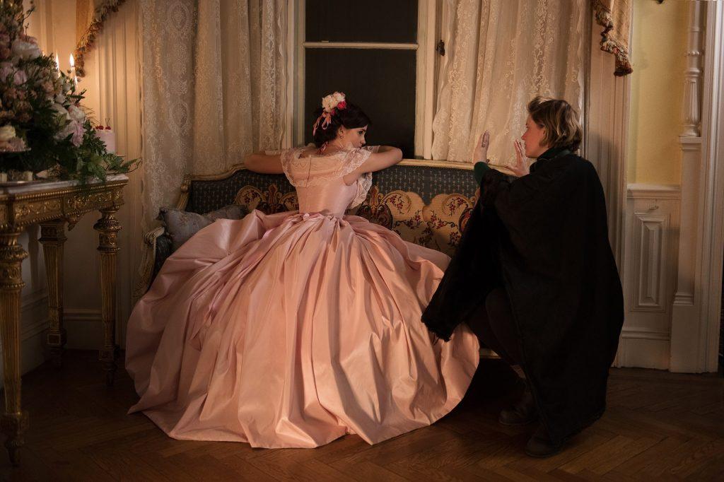Emma Watson, koja glumi Meg March, sjedi na klupici u ružičastoj haljini i sluša upute Grete Gerwig.
